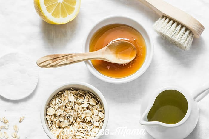 Closeup of honey, lemon, oats, olive oil and brush to make DIY beauty products