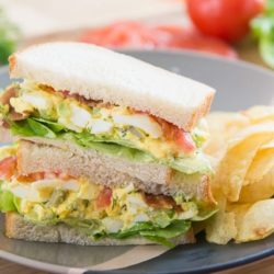 Egg Salad Stuffed Into Sandwiches With Tomato and Lettuce and Served with Chips