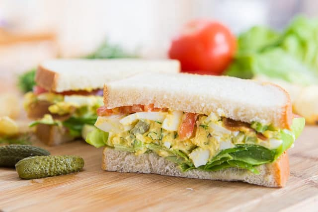 Egg Salad Sandwiches on a Wooden Board with Pickle